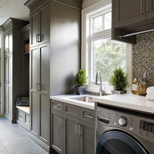 Aménagement d'une buanderie linéaire classique multi-usage avec un évier encastré, un placard à porte shaker, des portes de placard marrons, des machines côte à côte et un mur gris.