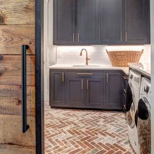 Idee per una lavanderia country con lavello a vasca singola, ante in stile shaker, ante blu, top in quarzo composito, pareti bianche, pavimento in mattoni, lavatrice e asciugatrice affiancate, pavimento rosso e top bianco