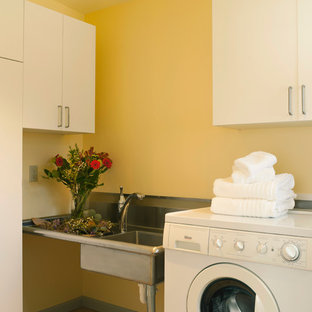 Small midcentury galley dedicated laundry room in Seattle with an undermount sink, flat-panel cabinets, white cabinets, stainless steel benchtops, yellow walls, ceramic floors and a side-by-side washer and dryer.