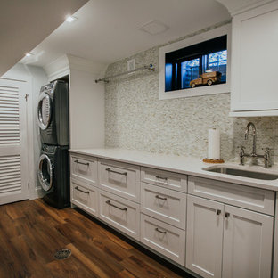 Design ideas for an expansive transitional single-wall dedicated laundry room in Denver with an undermount sink, shaker cabinets, white cabinets, quartz benchtops, grey walls, vinyl floors, a stacked washer and dryer, brown floor and white benchtop.