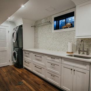 Idee per un'ampia sala lavanderia chic con lavello sottopiano, ante in stile shaker, ante bianche, top in quarzo composito, pareti grigie, pavimento in vinile, lavatrice e asciugatrice a colonna, pavimento marrone e top bianco