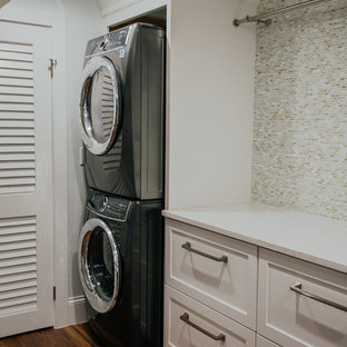 Inspiration for a huge transitional single-wall vinyl floor and brown floor dedicated laundry room remodel in Denver with an undermount sink, shaker cabinets, white cabinets, quartz countertops, gray walls, a stacked washer/dryer and white countertops