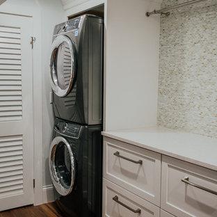 Klassisk inredning av en mycket stor vita linjär vitt tvättstuga enbart för tvätt, med en undermonterad diskho, skåp i shakerstil, vita skåp, bänkskiva i kvarts, grå väggar, vinylgolv, en tvättpelare och brunt golv