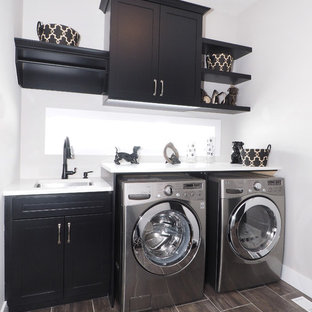 Mid-sized transitional single-wall brown floor dedicated laundry room photo in Toronto with an undermount sink, shaker cabinets, black cabinets, white walls, a side-by-side washer/dryer and white countertops