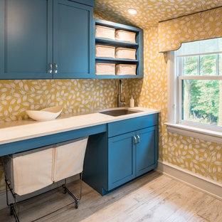 Inspiration för klassiska tvättstugor, med en undermonterad diskho, skåp i shakerstil, blå skåp och gula väggar