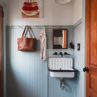 Ispirazione per una piccola lavanderia multiuso tradizionale con lavatoio, ante con riquadro incassato, ante blu, pareti blu, pavimento in legno verniciato, lavatrice e asciugatrice a colonna e pavimento blu