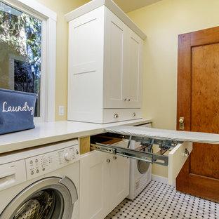 Exemple d'une buanderie parallèle craftsman dédiée et de taille moyenne avec un placard à porte shaker, des portes de placard blanches, un plan de travail en surface solide, un sol en marbre, des machines côte à côte, un plan de travail blanc et un mur beige.