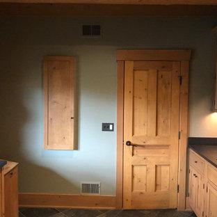 Exempel på en mellanstor klassisk svarta l-formad svart tvättstuga enbart för tvätt, med en rustik diskho, skåp i shakerstil, bruna skåp, granitbänkskiva, grönt stänkskydd, stänkskydd i trä, gröna väggar, skiffergolv, en tvättmaskin och torktumlare bredvid varandra och brunt golv