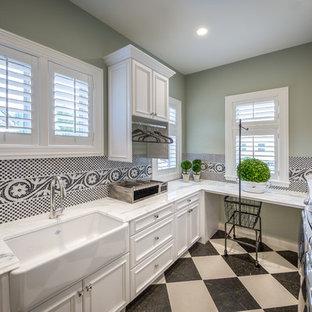 Foto på en mellanstor medelhavsstil u-formad tvättstuga enbart för tvätt, med en rustik diskho, luckor med infälld panel, vita skåp, granitbänkskiva, gröna väggar, klinkergolv i keramik, en tvättmaskin och torktumlare bredvid varandra och flerfärgat golv