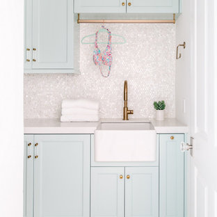Inspiration for a small beach style dedicated laundry room in Los Angeles with a farmhouse sink, recessed-panel cabinets, quartzite benchtops, white splashback, white walls, white benchtop, blue cabinets, mosaic tile splashback and grey floor.