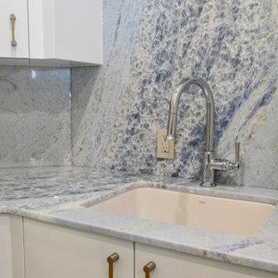 Exempel på en liten eklektisk blå linjär blått tvättstuga enbart för tvätt, med en undermonterad diskho, släta luckor, vita skåp, bänkskiva i kvartsit, blått stänkskydd, stänkskydd i sten, beige väggar, klinkergolv i porslin, en tvättpelare och beiget golv