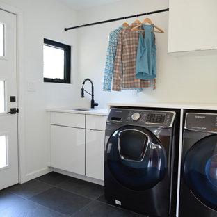 Exempel på en stor modern vita vitt tvättstuga, med en undermonterad diskho, släta luckor, skåp i ljust trä, bänkskiva i kvarts, vitt stänkskydd, stänkskydd i glaskakel, ljust trägolv och beiget golv