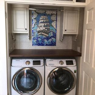 Ispirazione per una sala lavanderia country con ante a filo, ante grigie, top in legno, paraspruzzi con piastrelle in pietra, pavimento in travertino, lavatrice e asciugatrice nascoste, pavimento beige e top marrone