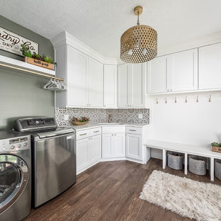 Example of a transitional l-shaped dark wood floor and brown floor utility room design in Columbus with an undermount sink, shaker cabinets, white cabinets, green walls, a side-by-side washer/dryer and white countertops