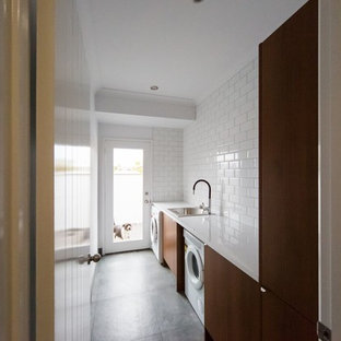 Inspiration for a small contemporary galley dedicated laundry room remodel in Brisbane with a single-bowl sink, flat-panel cabinets, medium tone wood cabinets, white walls and a side-by-side washer/dryer