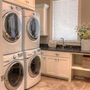 Idee per una lavanderia multiuso classica con lavello a vasca singola, ante bianche, top in marmo, pareti beige, pavimento in marmo e lavatrice e asciugatrice a colonna