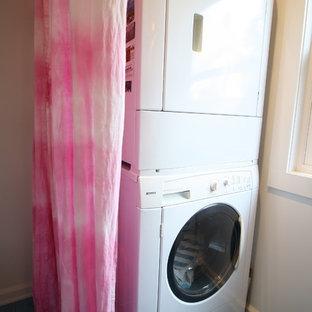 Idéer för att renovera en mellanstor funkis parallell tvättstuga enbart för tvätt, med släta luckor, vita skåp, bänkskiva i glas, beige väggar, klinkergolv i keramik, en tvättpelare och blått golv