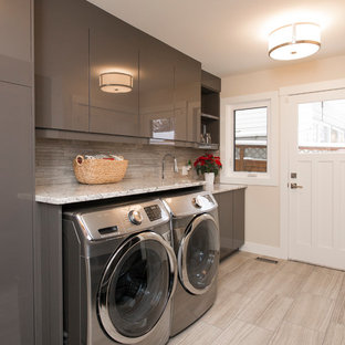 Dedicated laundry room - mid-sized transitional single-wall porcelain floor and gray floor dedicated laundry room idea in Calgary with flat-panel cabinets, gray cabinets, beige walls, a side-by-side washer/dryer, an undermount sink, quartz countertops and beige countertops