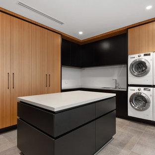Cette photo montre une buanderie tendance en L avec un évier 2 bacs, un placard à porte plane, des portes de placard en bois brun, des machines côte à côte, un sol gris et un plan de travail blanc.
