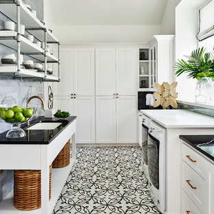 Classic galley utility room in Other with a submerged sink, shaker cabinets, white cabinets, white walls, a side by side washer and dryer, multi-coloured floors and black worktops.
