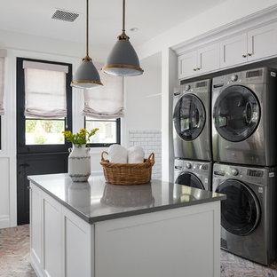Idées déco pour une buanderie classique avec un placard à porte shaker, des portes de placard grises, un mur blanc, un sol en brique, des machines superposées, un sol rouge et un plan de travail gris.