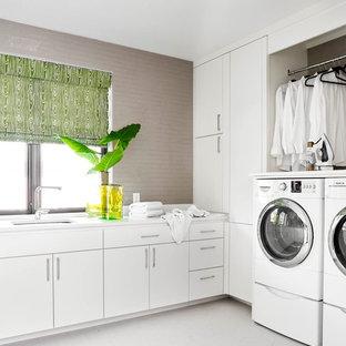 Idéer för en modern l-formad tvättstuga enbart för tvätt, med en undermonterad diskho, släta luckor, vita skåp, grå väggar och en tvättmaskin och torktumlare bredvid varandra