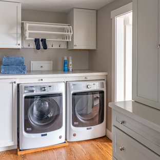 Photo of a mid-sized transitional single-wall dedicated laundry room in Boston with flat-panel cabinets, grey cabinets, grey walls, medium hardwood floors, a side-by-side washer and dryer, brown floor, white benchtop and laminate benchtops.