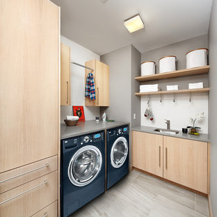 Inspiration for a contemporary l-shaped gray floor laundry room remodel in San Francisco with an undermount sink, flat-panel cabinets, light wood cabinets, gray walls, a side-by-side washer/dryer and gray countertops
