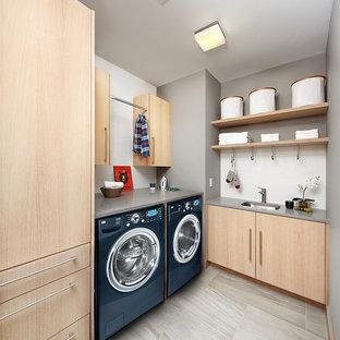 Modern inredning av en grå l-formad grått tvättstuga, med en undermonterad diskho, släta luckor, skåp i ljust trä, grå väggar, en tvättmaskin och torktumlare bredvid varandra och grått golv