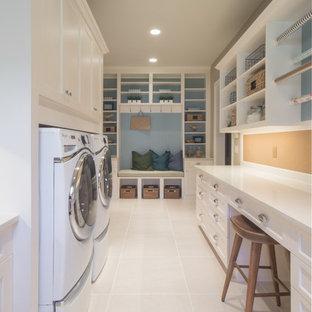 Klassisk inredning av en u-formad tvättstuga, med skåp i shakerstil, vita skåp och bänkskiva i kvarts
