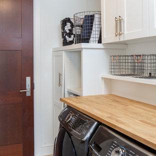 Réalisation d'une buanderie linéaire minimaliste dédiée et de taille moyenne avec un placard à porte shaker, des portes de placard blanches, un plan de travail en bois, un mur blanc, un sol en carrelage de céramique et des machines côte à côte.