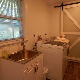 Klassisk inredning av ett mellanstort parallellt grovkök, med vita väggar, laminatgolv, en tvättmaskin och torktumlare bredvid varandra, brunt golv, en nedsänkt diskho, luckor med upphöjd panel och vita skåp