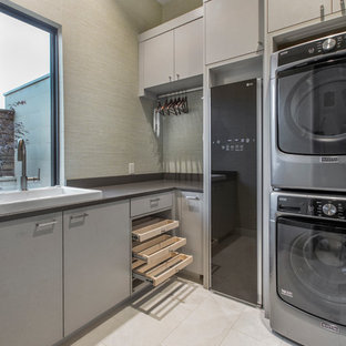 Inspiration for a small contemporary l-shaped separated utility room in Dallas with a built-in sink, flat-panel cabinets, a stacked washer and dryer, beige floors, grey cabinets, grey walls and black worktops.