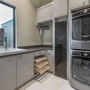 Immagine di una piccola sala lavanderia minimal con lavello da incasso, ante lisce, lavatrice e asciugatrice a colonna, pavimento beige, ante grigie, pareti grigie e top nero