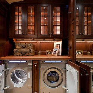 Laundry room - huge traditional carpeted and beige floor laundry room idea in Boston with glass-front cabinets, dark wood cabinets, a side-by-side washer/dryer and brown countertops