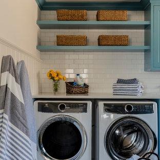 Maritim inredning av en mellanstor vita u-formad vitt tvättstuga enbart för tvätt, med en undermonterad diskho, skåp i shakerstil, blå skåp, bänkskiva i kvarts, vita väggar, klinkergolv i keramik, en tvättmaskin och torktumlare bredvid varandra och blått golv