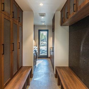 Immagine di una lavanderia multiuso minimal con lavello sottopiano, ante in stile shaker, ante in legno scuro, pareti bianche, lavatrice e asciugatrice affiancate, pavimento grigio e top grigio