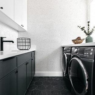 Immagine di una piccola sala lavanderia country con top in quarzo composito, pavimento in gres porcellanato, lavatrice e asciugatrice affiancate, pavimento nero, top bianco, lavello sottopiano, ante lisce, ante nere, pareti bianche e carta da parati