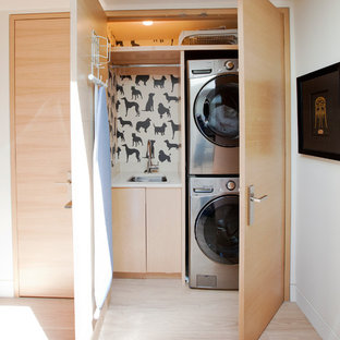 Exemple d'une buanderie linéaire tendance avec un placard, un évier encastré, un placard à porte plane, des portes de placard en bois clair, un mur blanc, un sol en bois clair, des machines superposées, un sol beige et un plan de travail blanc.