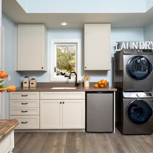 Example of a mid-sized beach style single-wall medium tone wood floor and brown floor utility room design in Santa Barbara with quartzite countertops, blue walls, a stacked washer/dryer, brown countertops, an undermount sink, shaker cabinets and beige cabinets
