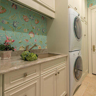 Inspiration for a large classic single-wall separated utility room in Miami with a submerged sink, multi-coloured walls, travertine flooring, a stacked washer and dryer, recessed-panel cabinets and beige cabinets.