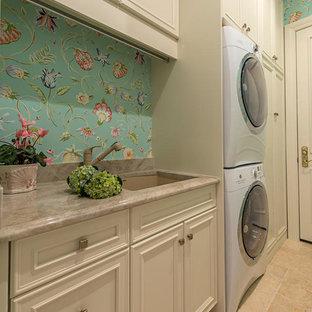 Immagine di una grande sala lavanderia classica con lavello sottopiano, pareti multicolore, pavimento in travertino, lavatrice e asciugatrice a colonna, ante con riquadro incassato e ante beige