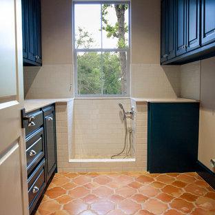 Inspiration för ett mellanstort medelhavsstil u-format grovkök, med luckor med upphöjd panel, blå skåp, granitbänkskiva, beige väggar, klinkergolv i terrakotta och en tvättmaskin och torktumlare bredvid varandra