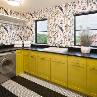 ミネアポリスの地中海スタイルのおしゃれな洗濯室 (L型、ドロップインシンク、シェーカースタイル扉のキャビネット、黄色いキャビネット、マルチカラーの壁、マルチカラーの床、黒いキッチンカウンター) の写真