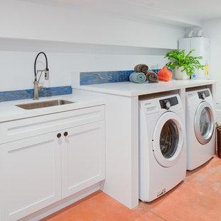 Idee per una grande lavanderia multiuso minimal con lavello da incasso, ante lisce, ante bianche, top in quarzo composito, pareti bianche, pavimento in cemento, lavatrice e asciugatrice affiancate, pavimento arancione e top bianco