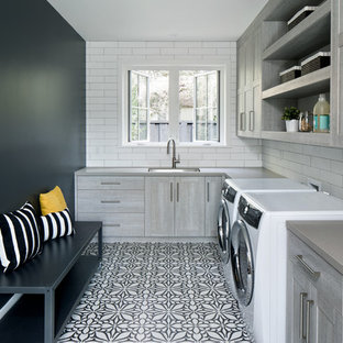 Example of a cottage laundry room design in San Francisco with a side-by-side washer/dryer, an undermount sink and black walls