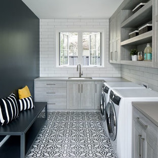 Laundry room - country l-shaped laundry room idea in San Francisco with an undermount sink, flat-panel cabinets, gray cabinets, black walls and a side-by-side washer/dryer