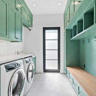 Esempio di una lavanderia multiuso country di medie dimensioni con ante in stile shaker, ante verdi, pareti grigie, pavimento in cemento, lavatrice e asciugatrice affiancate e pavimento grigio