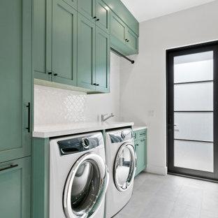 Exempel på ett mellanstort lantligt linjärt grovkök, med skåp i shakerstil, gröna skåp, grå väggar, betonggolv, en tvättmaskin och torktumlare bredvid varandra och grått golv