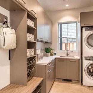 Immagine di una sala lavanderia moderna di medie dimensioni con lavello sottopiano, ante lisce, ante marroni, top in quarzo composito, pareti bianche, pavimento in gres porcellanato, lavatrice e asciugatrice a colonna, pavimento beige e top bianco